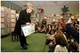 """Students at Vincenza Elementary School listen as Lynne Cheney reads her book """"America: A Patriotic Primer"""" during her visit to Caserma Ederle in Vicenza, Italy, Jan. 27, 2004."""