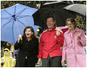 Jacalyn Leavitt, her husband, Health and Human Services Secretary Mike Leavitt and Education Secretary Margaret Spellings watch children run, fall and laugh as they run and slide on the South Lawn grass during the 2005 White House Easter Egg Roll.^M