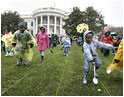 Children slip through a race with their Easter eggs during the traditional race on the South Lawn. Although rainy weather cut short the event, children and their parents made many colorful memories to brighten up a gray, gloomy day.^M