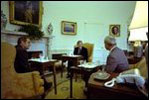 While sitting in front of the fireplace in the Oval Office February 7, 1977, President Jimmy Carter hosts a lunch for Vice President Mondale and energy adviser James Schlesinger. Hanging above the mantel is Charles Willson Peale's portrait of George Washington, which President Carter acquired for the White House's permanent art collection.