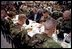 """President George W. Bush prays with troops before sharing Thanksgiving dinner at Fort Campbell, Ky., Nov. 21, 2001. """"This Thanksgiving, Americans are especially thankful for our freedom,"""" said the President. And we are especially thankful to you, the people who keep us free."""""""