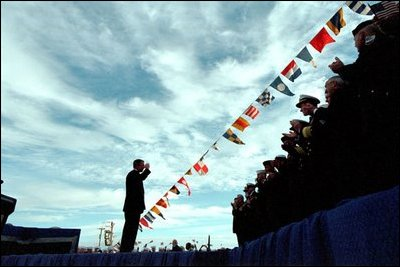"""President George W. Bush salutes navy personnel aboard the USS Enterprise in Norfolk, Va., on the 60th anniversary of the Pearl Harbor attack Dec. 7, 2001. """"Today we take special pride that one of our former enemies is now among America's finest friends,"""" said the President. """"We're grateful to our ally, Japan, and to its good people. Today our two Navies are working side by side in the fight against terror."""""""