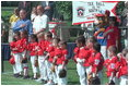 President George W. Bush and Cal Ripken stand for the singing of the national anthem during the opening ceremony of the first game of the White House Tee Ball season Sunday, May 5, 2002. Mr. Ripken is serving as the honorary commissioner of the White House T-ball League.