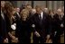 President George W. Bush escorts former First Lady Nancy Reagan to her seat before the funeral service for former President Ronald Reagan at the National Cathedral in Washington, DC on June 11, 2004.