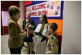 Hainerberg elementary students Montana Feix and Matt Bowlsby greet Laura Bush as she arrives to the school Tuesday, Feb. 22, 2005, in Wiesbaden, Germany. During her visit to the school Mrs. Bush heard a recital by the school chorus and talked with a group of fourth and fifth graders.