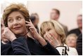 Laura Bush listens to translation headphones during a joint press conference with President George W. Bush and German Chancellor Gerhard Schroeder at the Electoral Palace in Mainz, Germany, Wednesday, Feb. 23, 2005. The Chancellor's wife, Mrs. Schroeder-Koepf is seated next to Mrs. Bush.