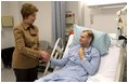 Laura Bush visits with U.S. Army Specialist Garrett Larson who is recovering from injuries sustained in Iraq at the Landstuhl Regional Medical Center Tuesday, Feb. 22, 2005, in Ramstein, Germany.