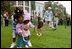 A helping hand is given during the Easter egg roll where little competitors use a spoon to carry a hard-boiled egg through the South Lawn race course and across the finish line at the White House Easter Egg Roll Monday, April 21, 2003.