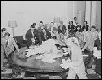 Reporters jump over tables in the White House to pick up press releases about the Japanese surrender, August 14, 1945.