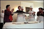 Mrs. Bush tries her hand at making fresh noodles during a Xian Culinary demonstration at the home of the U.S. Ambassador to China Thursday, February 21 2002 in Beijing. White House photo by Susan Sterner.