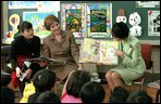 """Mrs. Bush and an interpreter listen as Princess Hisako Takamado reads a book she has written, """"Katie and the Dream-Eater"""", to students at Akashi Elementary School, Monday, February, 18, 2001. White House photo by Susan Sterner."""