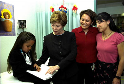 While promoting her <EM>Reach Out and Read</EM> program, Laura Bush reads to a child at the Kayenta Indian Health Service Clinic in Kayenta, Ariz., May 8, 2003.