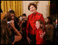 """Mrs. Laura Bush poses for a photo with a young guest following the performance of the Ford's Theater cast members presentation of """"A Christmas Carol,"""" Monday, Dec. 3, 2007, at the White House Children's Holiday Reception. White House photo by Shealah Craighead"""