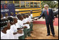 President George W. Bush is greeted by school children Thursday, Feb. 21, 2008, on his arrival to the University of Liberia to attend a education roundtable in Monrovia, Liberia. White House photo by Eric Draper