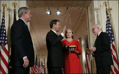 President George W. Bush watches Thursday, Sept. 29, 2005 in the East Room of the White House in Washington, as Judge John G. Roberts is sworn-in as the 17th Chief Justice of the United States by Associate Supreme Court Justice John Paul Stevens. Judge Roberts' wife Jane is seen holding the Bible.