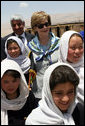 Mrs. Laura Bush is joined by Ihsan Ullah Bayat, top let, and young Afghan girls during a tour of the construction site of the Ayenda Learning Center Sunday, June 8, 2008, in Bamiyan, Afghanistan. White House photo by Shealah Craighead