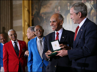 President George W. Bush presents the Congressional Gold Medal Dr. Roscoe Brown Jr., during ceremonies honoring the Tuskegee Airmen Thursday, March 29, 2007, at the U.S. Capitol. Dr. Brown, Director of the Center for Urban Education Policy and University Professor at the Graduate School and University Center of the City University of New York, commanded the 100th Fighter Squadron of the 332 Fighter Group during World War II. White House photo by Eric Draper