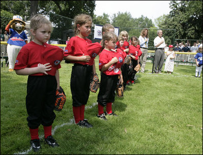 Members of the Luray, Virginia Red Wings hold their caps over their hearts during the playing of the national anthem Wednesday, June 27, 2007, prior to the start of the 2007 White House Tee Ball opener against the Bobcats of Cumberland, Maryland.