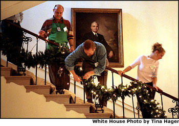 Under the watchful gaze of Harry S. Truman's portrait, volunteers Mike Bickley (left), David Padua (center) and Samantha Rutledge hang garland on the Grand Staircase, which leads from the Grand Foyer up to the President's residence. White House photo by Tina Hager.
