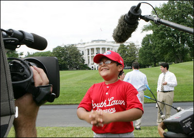 A player with the Cramer Hill Little League Red Sox of Camden, N.J., is the center of media attention on the South Lawn of the White House after playing Monday, June 30, 2008, in the opening game of the 2008 Tee Ball on the South Lawn, with his teammates against the Jose M. Rodriguez Little League Angels of Manatí, Puerto Rico.