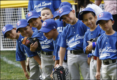 Players of the Jose M. Rodriguez Little League Angels of Manatí, Puerto Rico, all look over toward President George W. Bush as he welcomes everyone to the 2008 Tee Ball on the South Lawn Season Opener Monday, June 30, 2008, on the South Lawn of the White House.