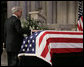 Newsman Tom Brokaw places his hand on the casket of former President Gerald W. Ford, as he makes his way to the lectern to deliver his remarks during the State Funeral service Tuesday, Jan. 2, 2007, at the National Cathedral in Washington, D.C. White House photo by Eric Draper
