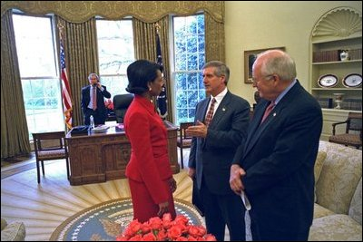 Chief of Staff Andy Card talks with National Security Advisor Dr. Condoleezza Rice and Vice President Dick Cheney as President Bush talks on the phone in the Oval Office March 18, 2003.