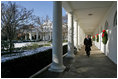President George W. Bush takes a brisk walk along the colonnade in the Rose Garden Friday morning, Dec. 9, 2005.