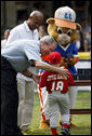 President George W. Bush presents Angel Tavarez, of the Cramer Hill Little League Red Sox from Camden, New Jersey, with a baseball Monday, June 30, 2008, following the opening game of the 2008 Tee Ball on the South Lawn. President Bush is joined on the field by Roberto Clemente, Jr. and Dugout, the Little League mascot. White House photo by Eric Draper