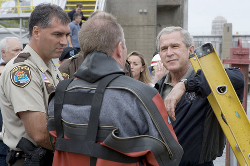 President George W. Bush listens to a search and rescue diver describe the scene in the Mississippi River during his visit to the Interstate 35W bridge collapse in Minneapolis, Saturday, Aug. 4, 2007. President Bush praised the work of first responders, local authorities and investigators in their response to the tragic bridge collapse. White House photo by Chris Greenberg