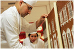 Thaddeus DuBois, Head Pastry Chef, places columns of white chocolate onto of the official White House gingerbread house.