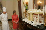 Laura Bush is shown the White House gingerbread house by White House pastry chef Thaddeus DuBois, on display in the State Dining Room.