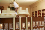 Thaddeus DuBois, Head Pastry Chef, places the roof on top of the White House gingerbread house.