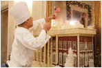 White House pastry chef Thaddeus DuBois tops off his gingerbread house with a flag, Wednesday, Nov. 30, 2005, in the State Dining Room, as the finishing touches are made to the White House Christmas decorations.