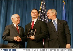 President George W. Bush and U.S. Attorney General Michael Mukasey congratulate FBI special agent graduate Richard Brooks, center, after he is presented with the Director's Leadership Award Thursday, Oct. 30, 2008, during the graduation ceremony for FBI special agents in Quantico, Va. White House photo by Joyce N. Boghosian