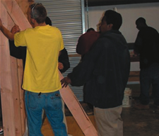 Image of multiple people framing a house