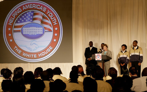 """Mrs. Laura Bush is joined on stage by Ballou High School Marching Band Director Darrell Watson, left, band members Lewis Franklin, Rhia Hardman and Kenneth Horne, right, as she addresses students and guests at the White House Thursday, Oct. 11, 2007, prior to a screening of Ballou: A Documentary Film, about the Washington, D.C. band's inspiring accomplishments. Mrs. Bush said, """"Mr. Darrell Watson epitomizes the core message of the Helping America's Youth initiative-that caring adults can have a powerful impact on the lives of our nation's youth."""" White House photo by Shealah Craighead"""