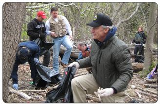 Secretary Kempthorne joins Take Pride in America, DOI employees, and Living Lands and Waters in the Capital River Relief cleanup.  He and the other volunteers helped pick up trash along the shore of  the Potomac River .  Last year, Capital River Relief volunteers collected 70 tons of garbage over a 30 mile span of the Potomac River.