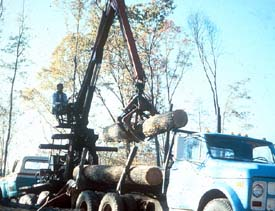 Knuckle boom unloading logs from log truck