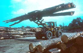 Tractor carrying logs through yard in unstable manner
