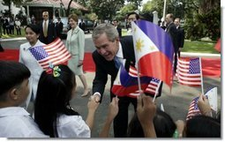 President George W. Bush, Philippine President Gloria Arroyo and Laura Bush greet school children during a welcoming ceremony at Malacanang Palace in Manila, Philippines, Saturday, Oct. 18, 2003.  White House photo by Paul Morse