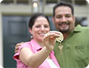 A happy man and woman; the woman is holding the keys to their new home.