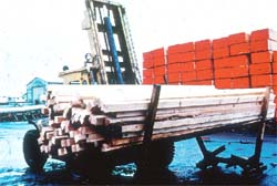 A powered industrial truck moves lumber.
