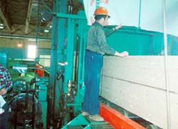 A worker bands and wraps a lumber package.