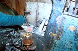 A worker manually adjusts tolerances of cutting heads with the machine running.