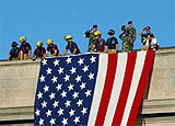 Firefighters draping an American flag off the roof of the Pentagon