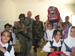 Army Staff Sgt. Patrick Leon (standing, center) with Iraqi soldiers and students at the Al Awaas Mixed Primary School in Baghdad. Photo courtesy of the Army