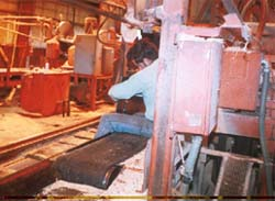 Worker sitting on belt conveyor. This is not a safe practice.