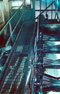 Roller conveyor with unguarded chain and sprocket drives.