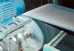Unguarded nip point between belt and pulley on belt conveyor.